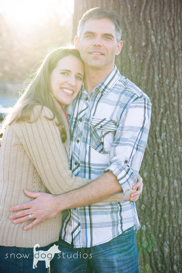 Sun peeking over the shoulder of a couple during a family photography session in Waxhaw